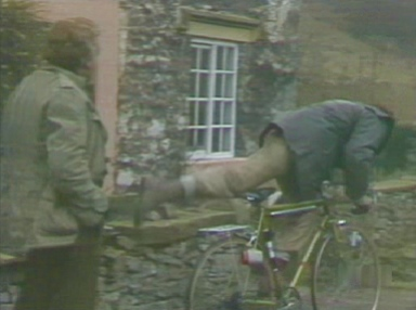Charles mounts the bike, and pedals away