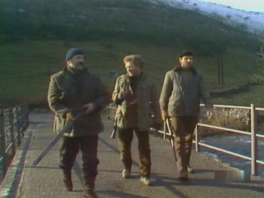 Sanders, Phil and Jim walk across the bridge warily as the dogs scatter