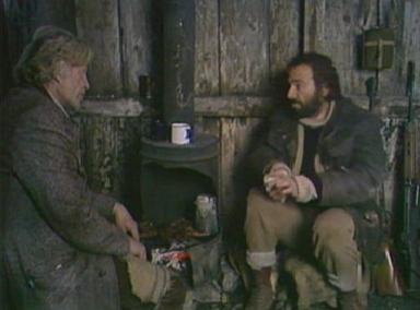Charles and Fenton dine on rabbit in the wooden hut